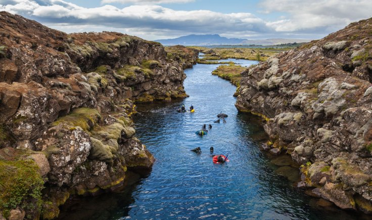 Seen here are a group of snorkelers at the Silfra canyon, a rift between the tectonic plates (North American and Eurasian) at Þingvellir National Park, Southern Region, Iceland. Silfra was formed as a consequence of the two tectonic plates drifting apart. Each year, the plates drift about 2 cm farther apart, which builds up tension between the plates and the earth mass above. This tension is released through a major earthquake approximately every ten years. In these earthquakes, cracks and fissures are formed in Þingvellir. Silfra is one of the largest cracks and started with a deep cave where most of the underwater wells feed it. The site lies at the rim of the Þingvallavatn Lake.